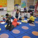 Students working on the rug at E.N. White in the dual language class