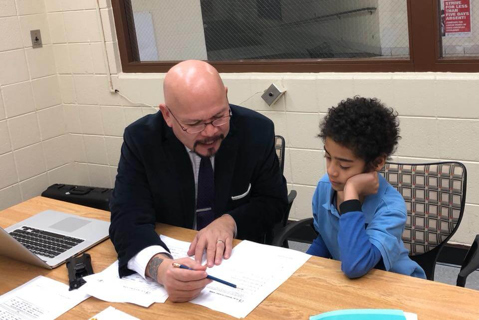 Principal Soria working with a student