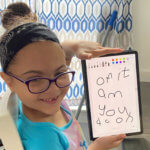 Holyoke Update girl in blue shirt with glasses is holding white board with writing