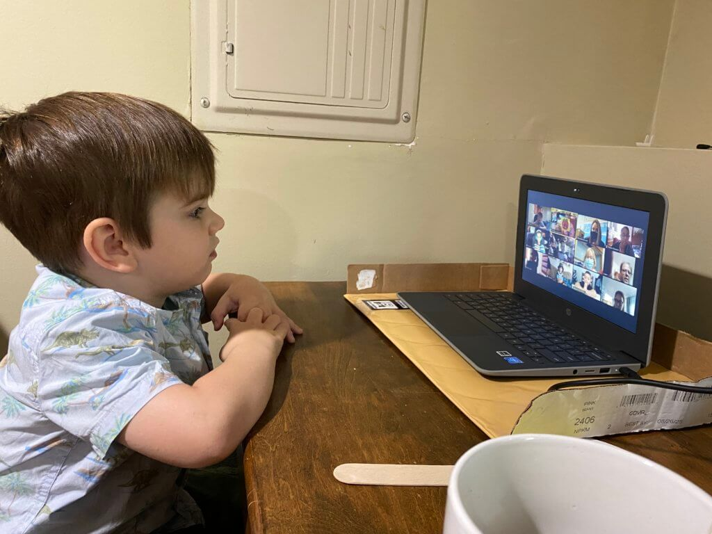 young boy at home participating in remote learning using a laptop