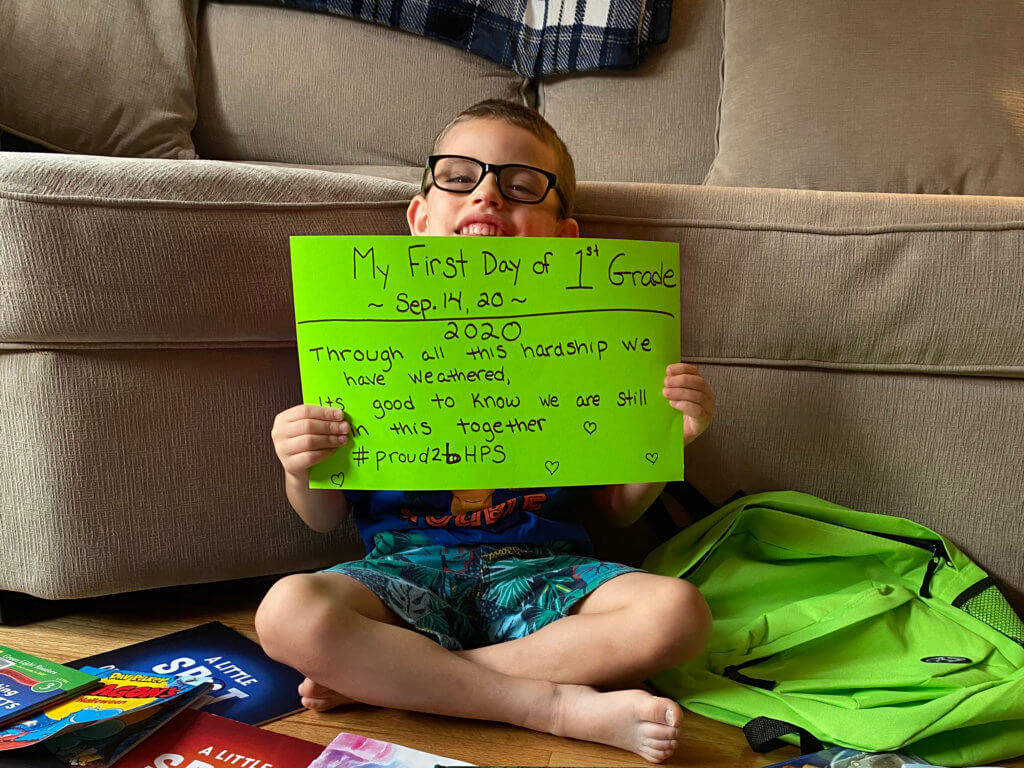 First day of school 2020 - boy wearing glasses is seated holding a green 1st day sign