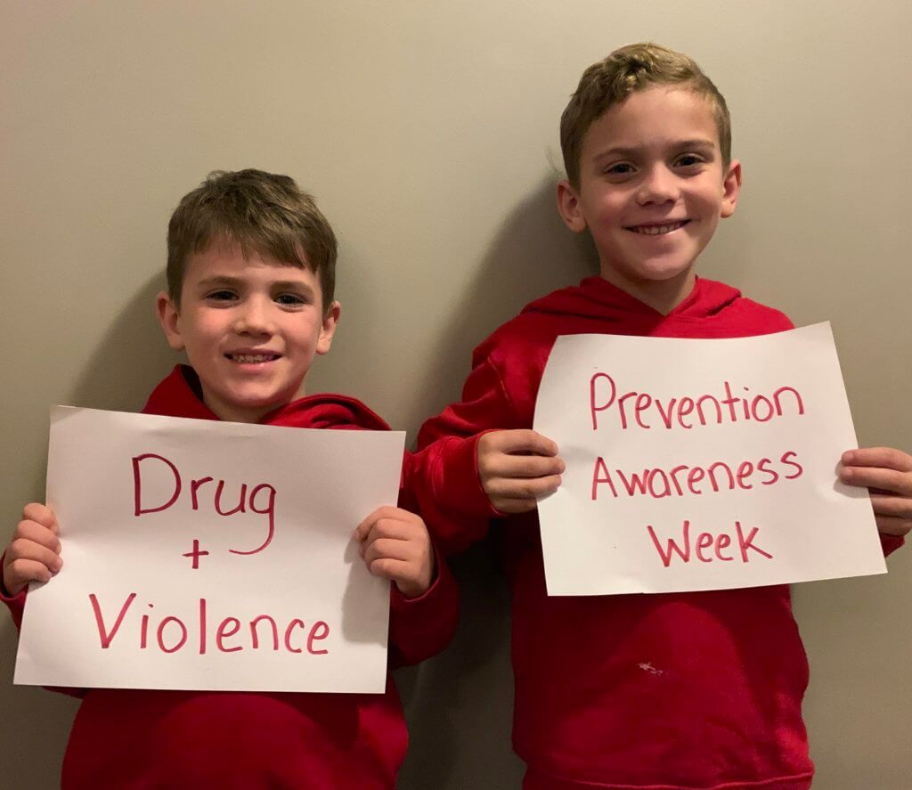 two male students wearing red for drug and violence prevention awareness