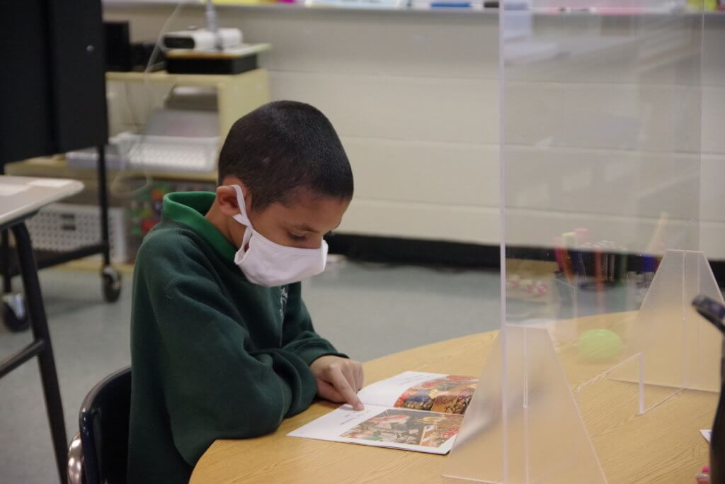 11-5-20 Holyoke Update male student with mask at table reading book