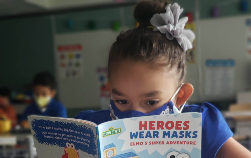 female student in blue shirt with hair in bun wears mask and reads book Heroes Wear Masks