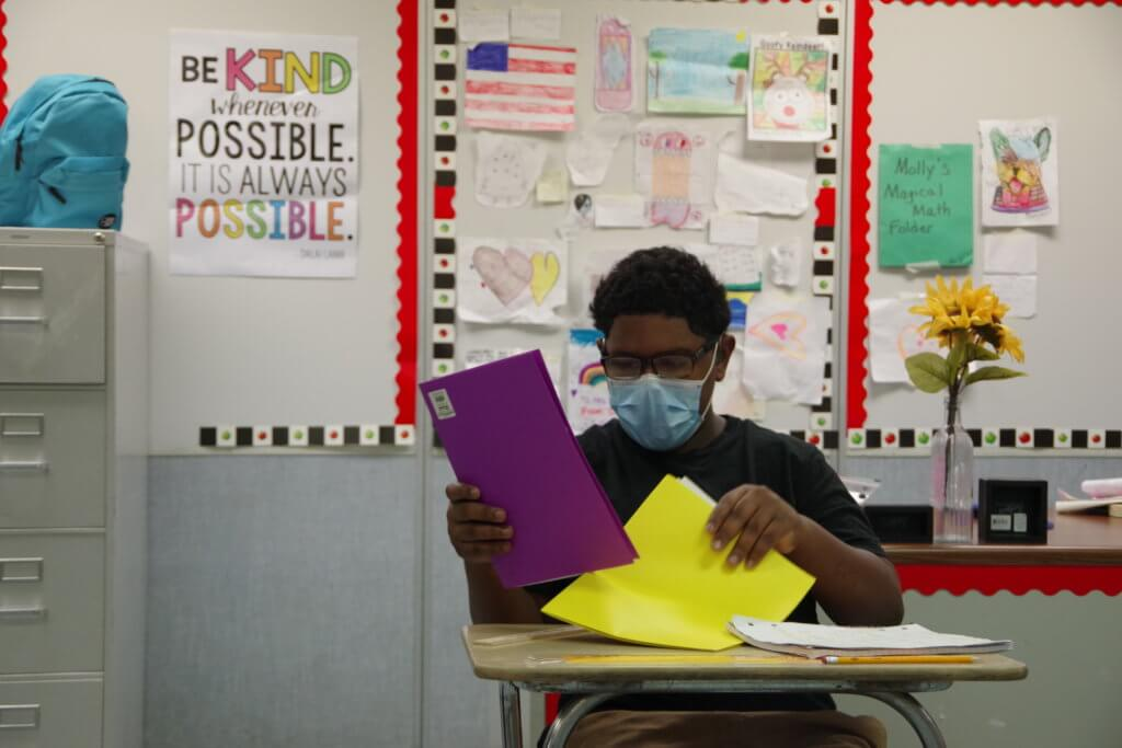 Male high school student sitting at desk with yellow and purple folders