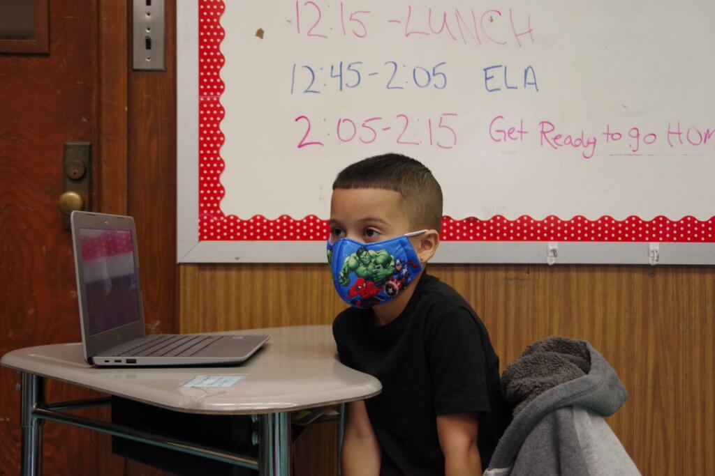 male student seated at desk with laptop wearing a blue mask and black t-shirt with whiteboard in the background schedule
