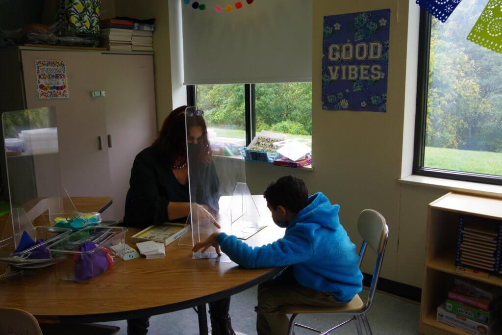 teacher and student working at table with plexiglasss masks