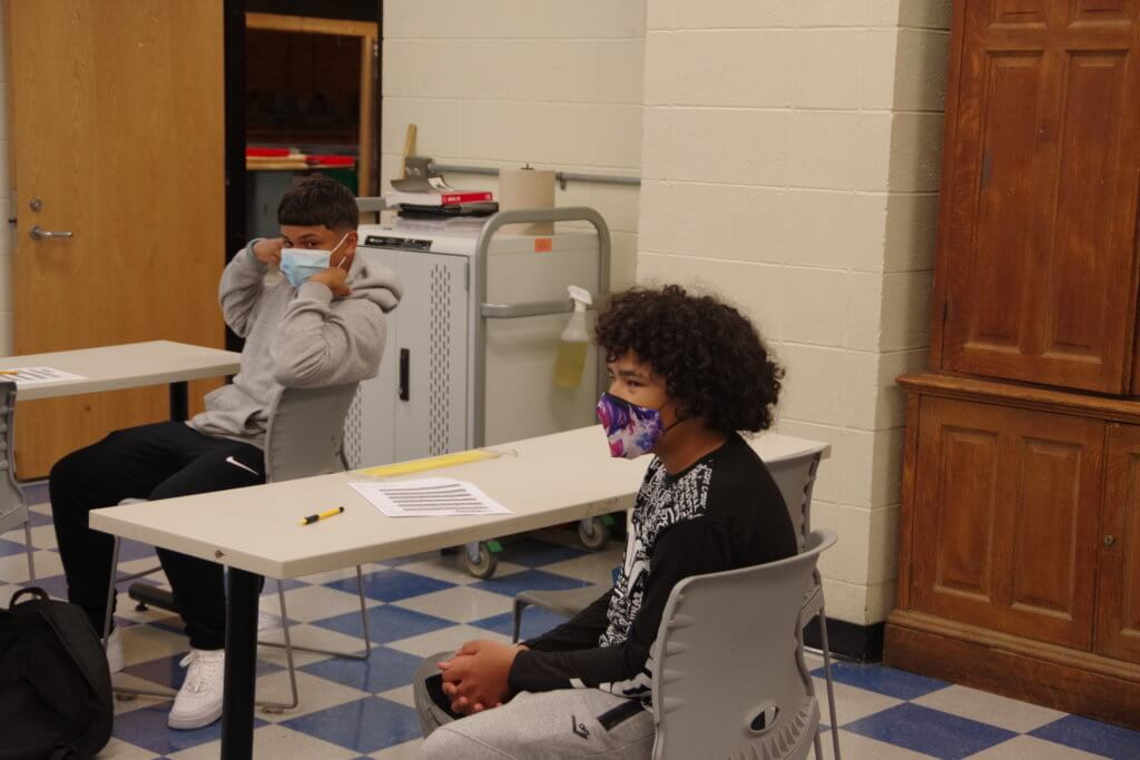 2 male dean students seated in classroom with masks