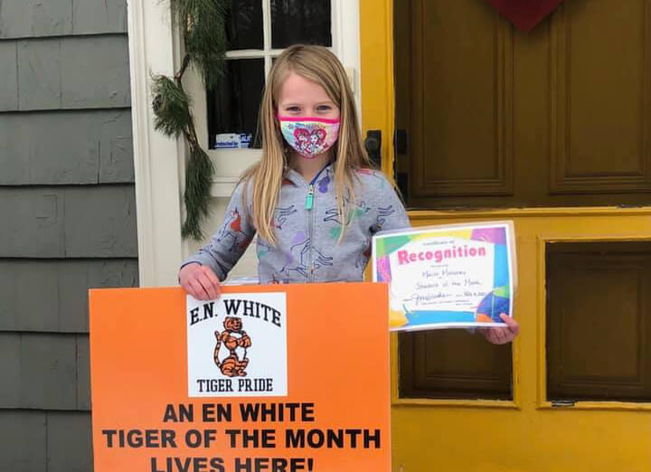 Female student wearing a mask holding a Tiger of the Month poster in front of doorstep