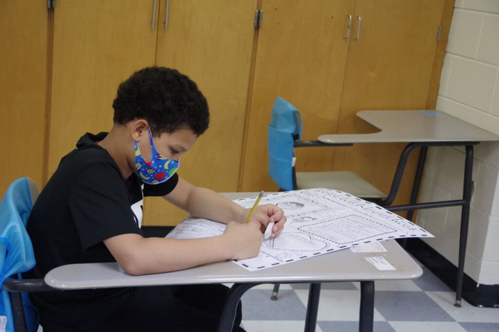male student seated at desk wearing a mask and black tshirt