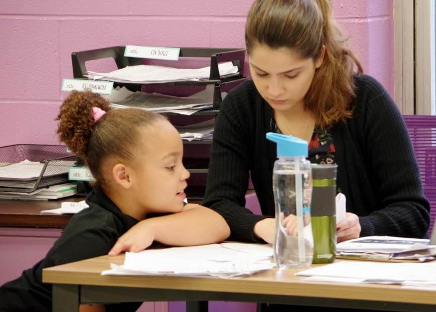 Veritas female teacher seated at table while working with female student