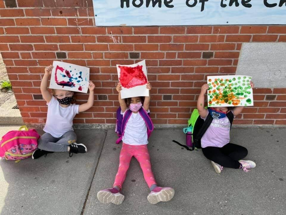 McMahon female students holding up artwork in front of the school