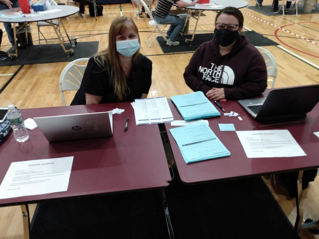 staff sitting at intake table at vaccination clinic
